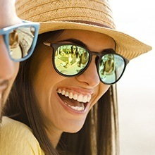 Smiling woman with glasses and sun hat