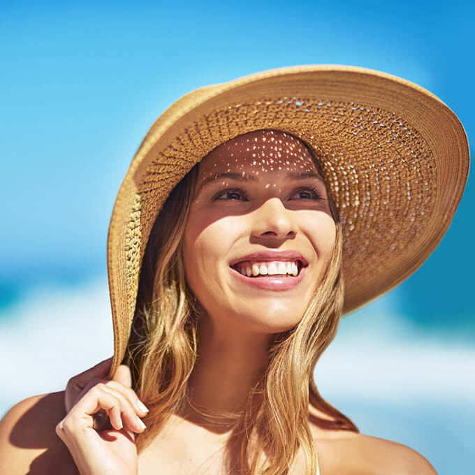Smiling woman at beach wearing sun hat