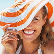 Woman with brilliant white smile covering half of face with sun hat