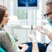 A dentist discussing dental implants with a female patient