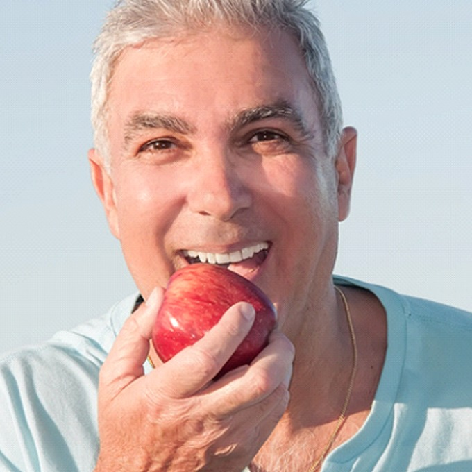 Older man and woman laughing and holding hands