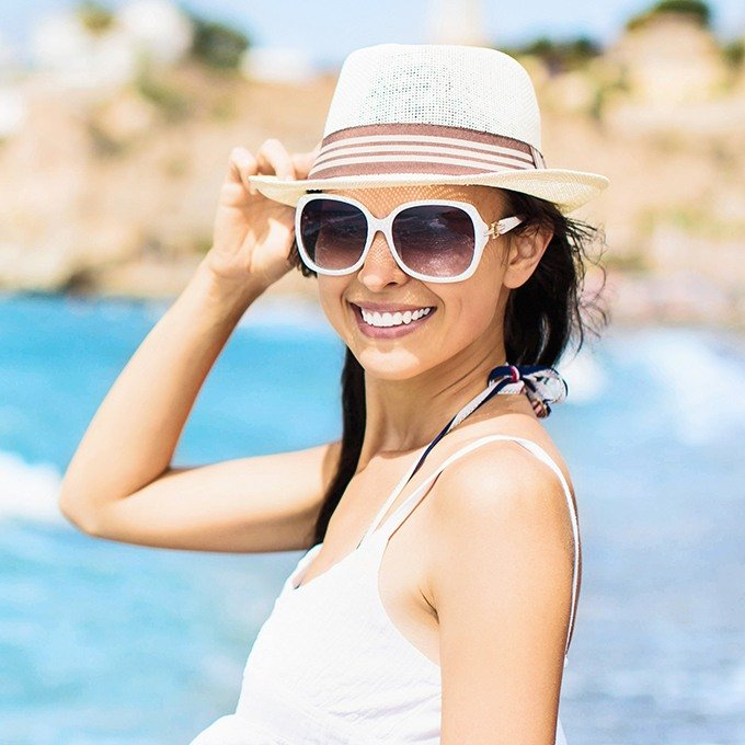 Young woman with sunglasses and hat at the beach