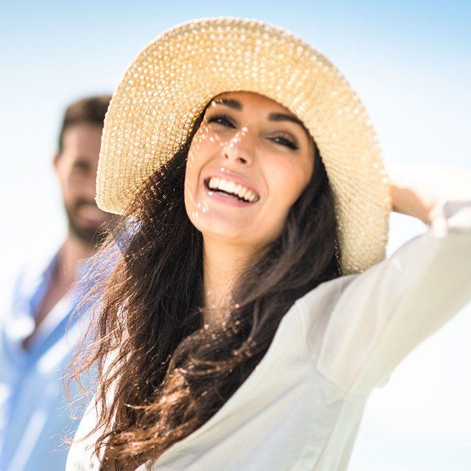 Smiling woman at beach wearing large sun hat