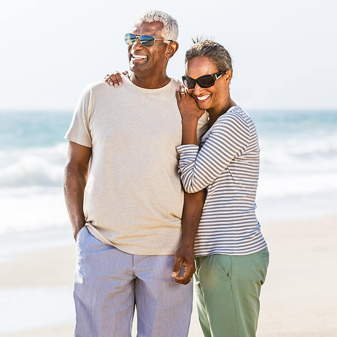 Older man and woman smiling at beach