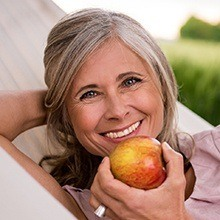 Older woman smiling and holding an apple