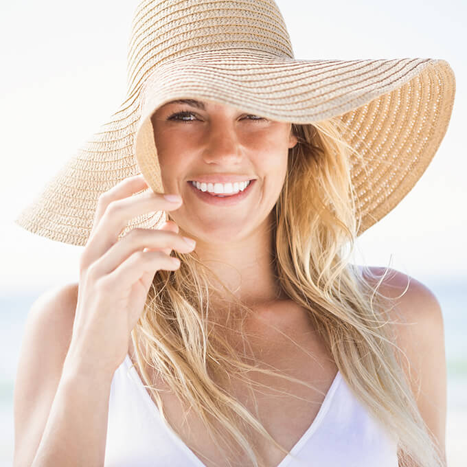 Woman with beautiful smile wearing large hat