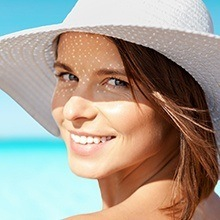Smiling woman at beach with sun hat