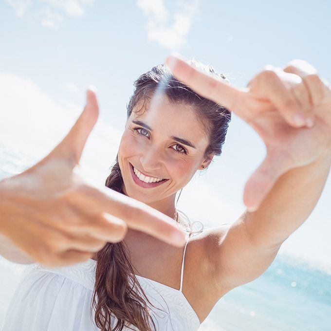 Smiling woman at beach making photo frame with hands