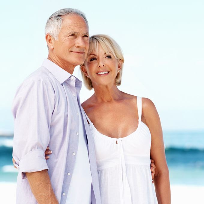 Older couple on beach smiling