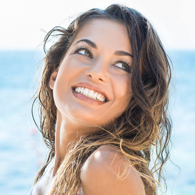 Young woman at beach with gorgeous smile