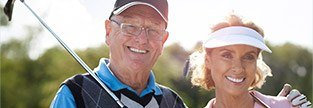 Two older patients smiling on golf course
