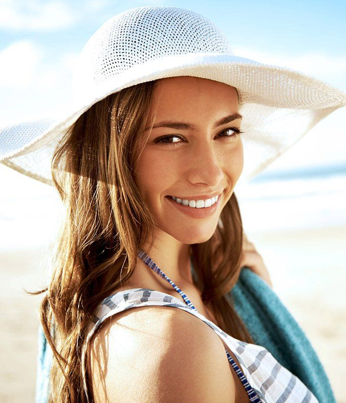 Smiling woman in a sun hat at beach