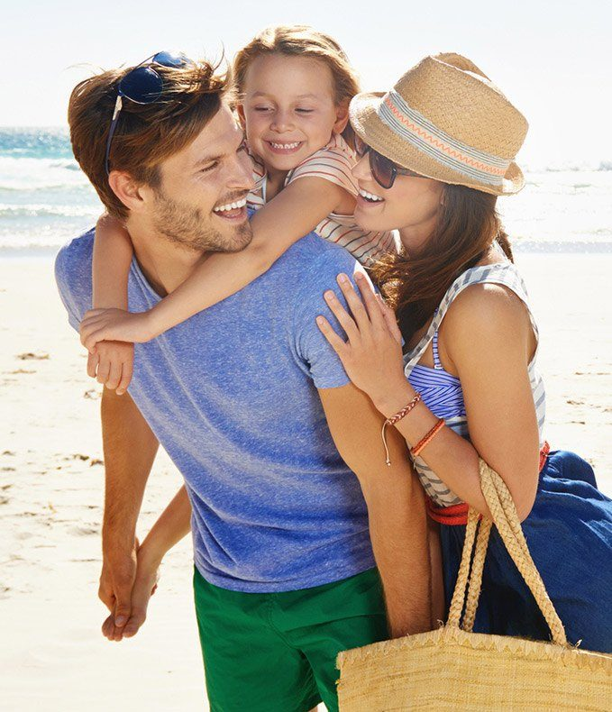 Happy family laughing on the beach