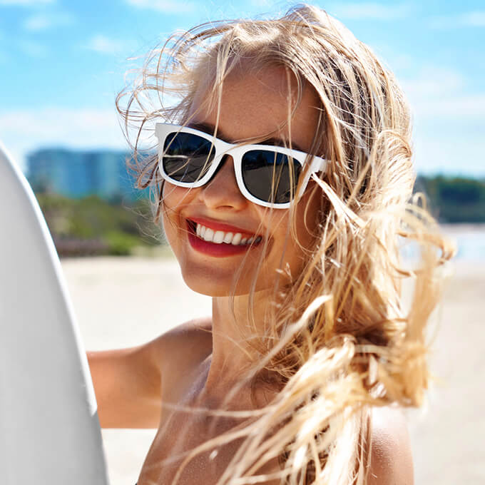Young woman at beach holding surf board