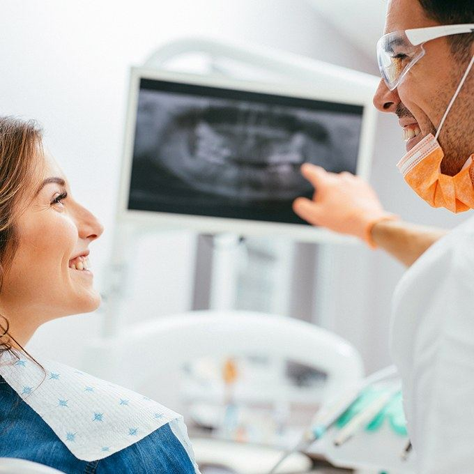 Smiling woman and dentist looking at x-rays
