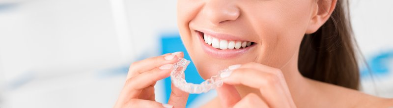 attractive young woman inserting invisalign