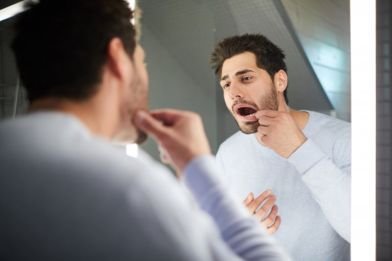 Man checking his teeth in the mirror